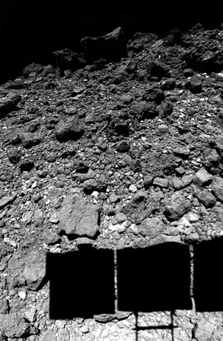 The surface of asteroid Ryugu, as observed by the Hayabusa2 spacecraft just before  landing. The spacecraft's solar panels cast a shadow on the surface.